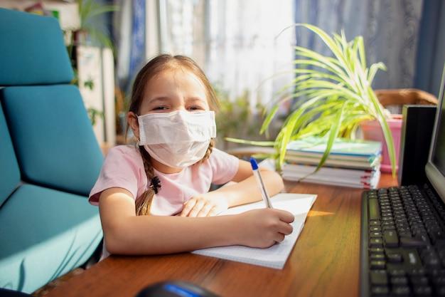 La scolara della ragazza in una mascherina medica fa i compiti davanti ad un computer. quarantena e scuola a casa