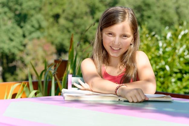 La scolara impara le sue lezioni sul tavolo del giardino