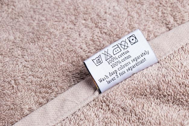 La scritta 100% di gatti su un asciugamano di spugna sdraiato su uno sfondo rosa