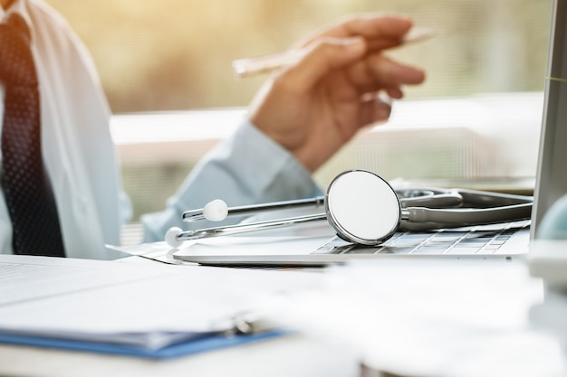 La scrittura del medico della medicina sul computer portatile in ufficio medico.