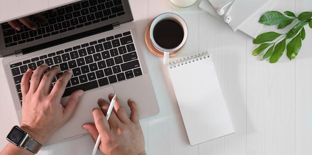 La scrittura dell'uomo d'affari sulla tastiera del computer portatile