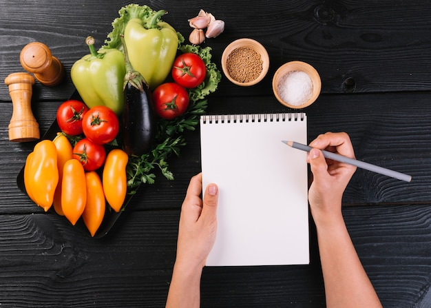 La scrittura della mano della persona sul blocco note a spirale vicino alle verdure e alle spezie su superficie di legno nera
