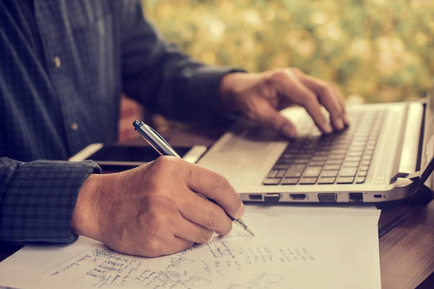 La scrittura della penna di tenuta dell'uomo d'affari sul funzionamento del documento cartaceo, fine sulla mano scrive il lavoro di ufficio