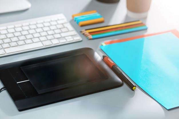 La scrivania grigia con laptop, blocco note con foglio bianco, vaso di fiori, stilo e tablet per ritocco