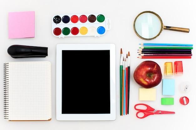 La scuola ha messo con i taccuini, le matite, la spazzola, le forbici e la mela su bianco