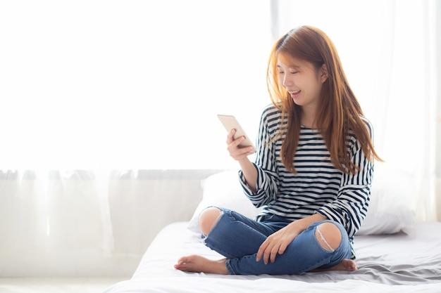 La seduta sorridente della bella donna asiatica si rilassa sul letto
