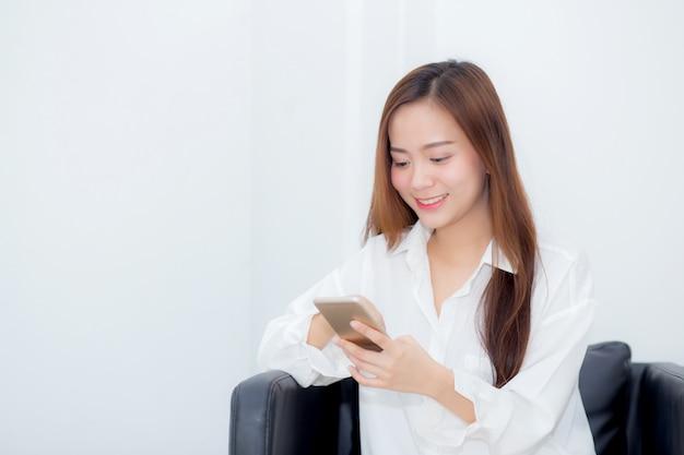 La seduta sorridente della bella donna asiatica si rilassa sulla sedia