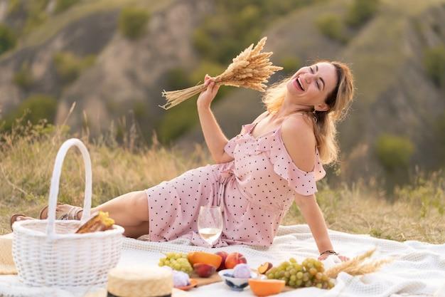 La sera, la donna si gode un picnic in una calda giornata estiva.