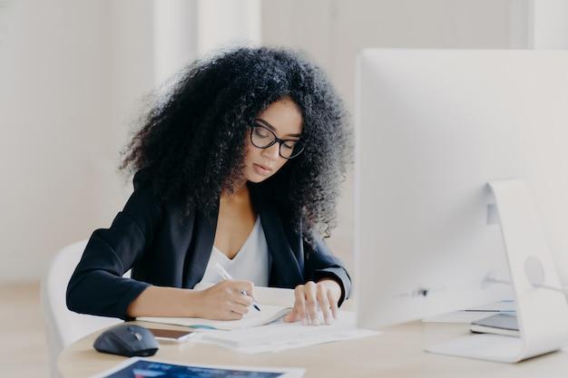 La seria donna afro scrive sui giornali, si siede al tavolo con un computer moderno, crea articoli di giornale
