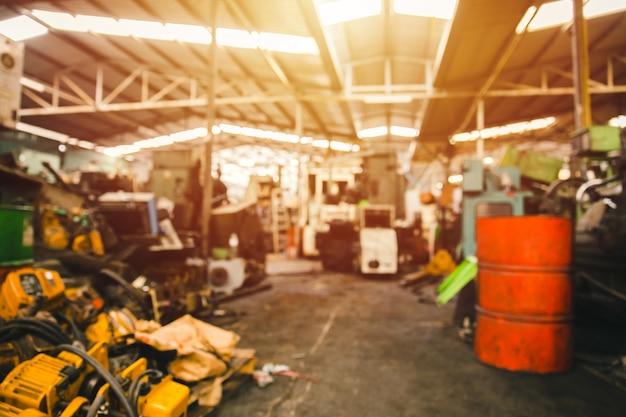 La sfocatura ha usato il garage dell'officina del macchinario o il magazzino della discarica della macchina pesante