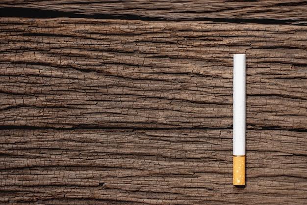 La sigaretta è posta su un vecchio pavimento di legno.