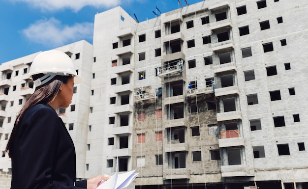 La signora afroamericana in casco di sicurezza con le carte si avvicina alla costruzione in costruzione