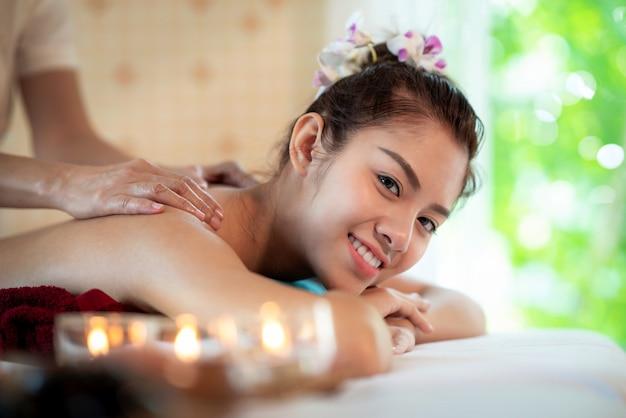 La signora asiatica nel negozio della stazione termale e si rilassa dal massaggio tailandese dell'olio