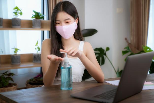 La signora asiatica usa la maschera per il viso e la pulizia delle mani con gel alcol per prevenire il virus corona