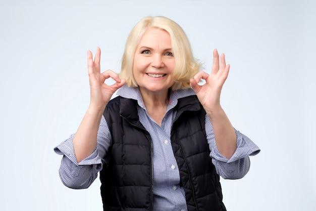 La signora bionda senior sorridente mostra il segno giusto