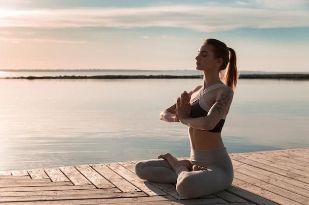 La signora dello sport in spiaggia fa esercizi di meditazione.