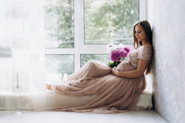 La signora in attesa si trova sul davanzale della finestra in una stanza luminosa