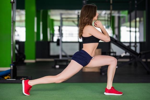 La signora in palestra sta facendo diversi esercizi per rendere il suo corpo più forte