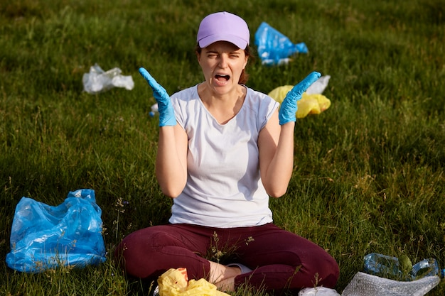 La signora in preda al panico, seduta sul terreno in campo, urlando, scioccata dall'inquinamento, deve raccogliere un sacco di spazzatura, indossare un abbigliamento casual, avere un'espressione facciale arrabbiata.