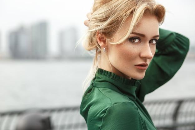 La signora splendida in vestito verde posa prima di un fiume a new york