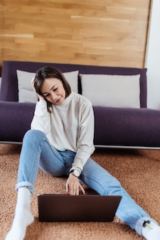 La signora stanca lavora al computer portatile che si siede sul pavimento a casa nel tempo casuale vestita