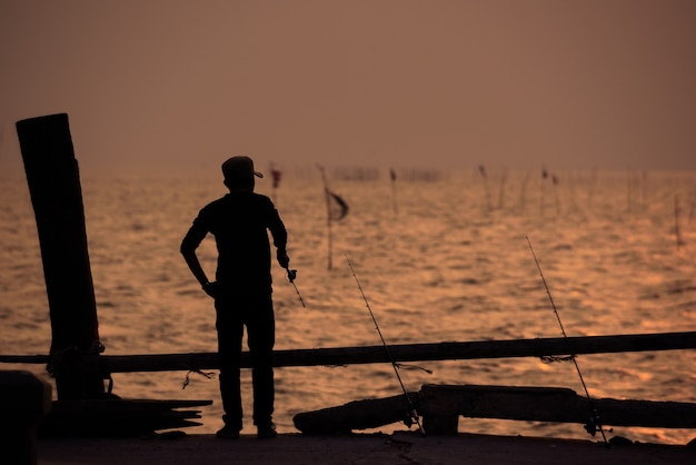 La silhouette del pescatore con il cielo al tramonto