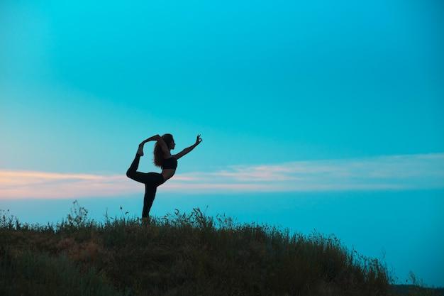 La silhouette della giovane donna sta praticando lo yoga