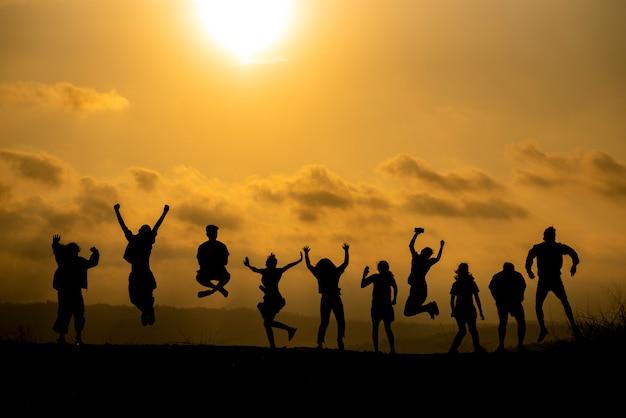 La silhouette di un gruppo di persone sta celebrando il successo in cima alla collina.