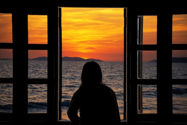 La silhouette di una giovane donna che guarda attraverso la finestra con vista sul mare.