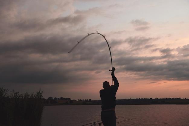 La siluetta del pescatore getta una canna da pesca nel lago al tramonto