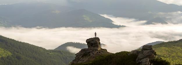 La siluetta del turista atletico dello scalatore su alta formazione rocciosa sulla valle della montagna ha riempito di nuvole e nebbia gonfie bianche e coperte di pendii di montagna sempreverdi della foresta nell'ambito del chiaro fondo del cielo.