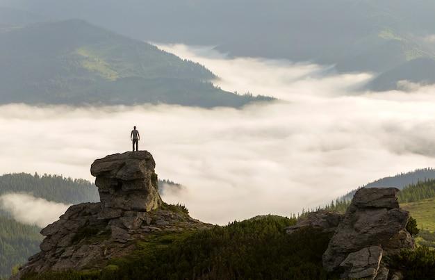 La siluetta del turista atletico dello scalatore su alta formazione rocciosa sulla valle della montagna ha riempito di nuvole e nebbia gonfie bianche.