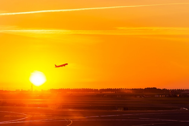 La siluetta dell'aeroplano, aereo, decolla su aria a tempo del tramonto w