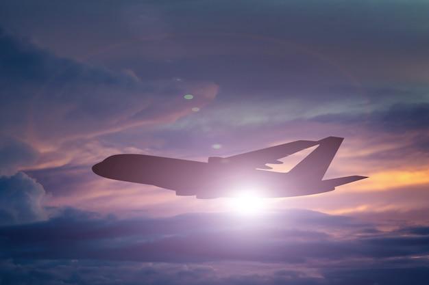 La siluetta dell'aeroplano decolla sul cielo drammatico variopinto con la nuvola al fondo del tramonto.