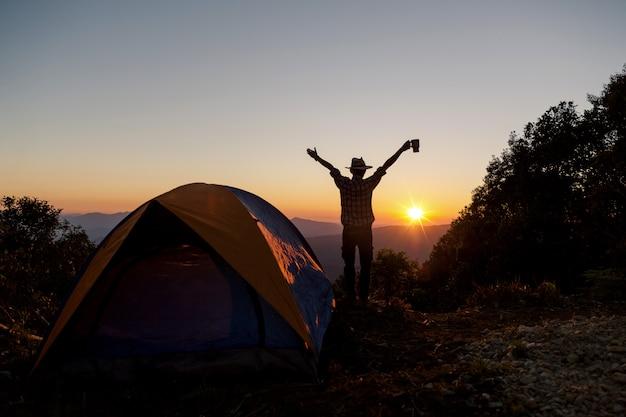 La siluetta dell'uomo felice con la tazza di caffè della tenuta resta vicino alla tenda intorno alle montagne