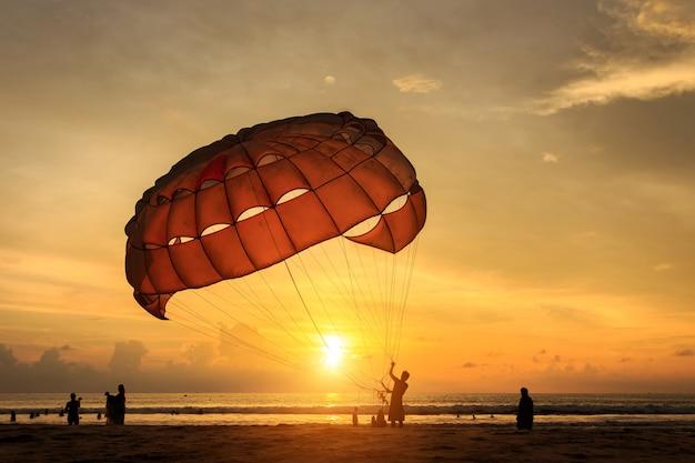 La siluetta dell'uomo sta preparando la navigazione di para alla spiaggia del tramonto in tailandia