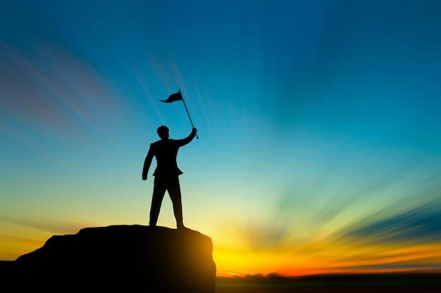 La siluetta dell'uomo sulla cima della montagna sopra cielo e il sole accendono il concetto di successo, della direzione e della gente