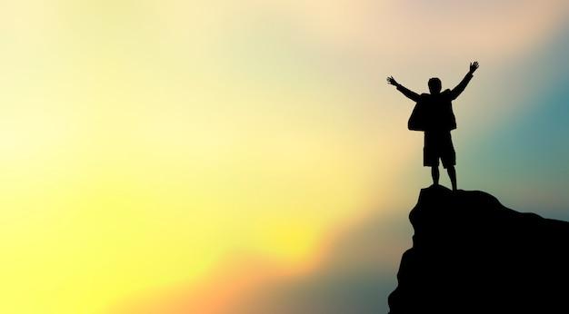 La siluetta dell'uomo sulla cima della montagna sopra il cielo e il sole si accendono