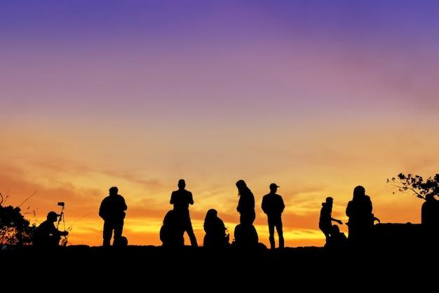 La siluetta della gente del gruppo viaggia la vacanza felice sulla vista della scogliera la loro alba.