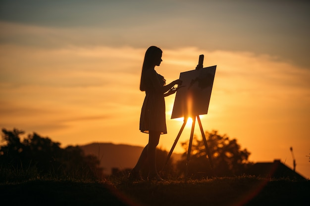 La siluetta della ragazza bionda dipinge un dipinto sulla tela. tavolozza con vernici e spatola, giornata di sole estivo
