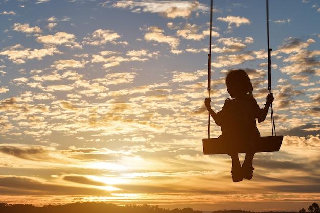 La siluetta della ragazza del bambino è oscillazione nel fondo del tramonto.