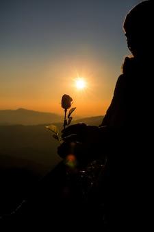 La siluetta della tenuta delle coppie è aumentato sulla collina all'orizzonte di tempo del tramonto su fondo