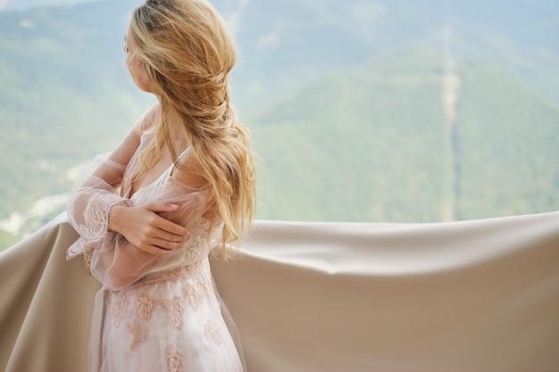 La siluetta di giovane bella sposa in un peignoir sta sul balcone