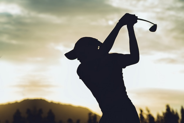 La siluetta di giovane giocatore di golf femminile ha colpito spazzare e mantiene il campo da golf che fa l'oscillazione di golf, si esercita per il tempo di rilassamento