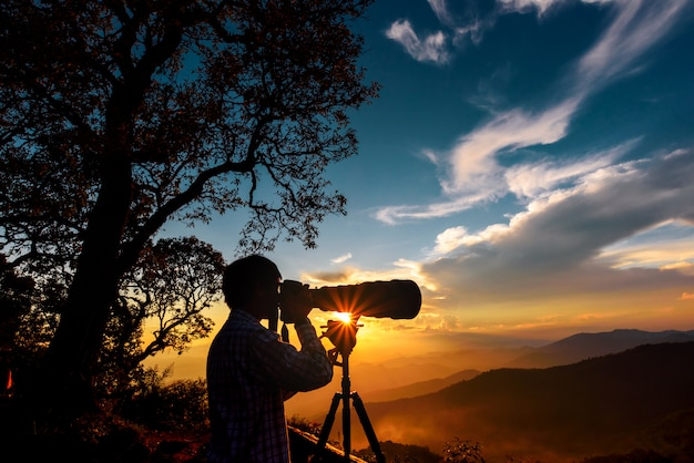 La siluetta di un fotografo di paesaggio usa il teleobiettivo eccellente in cima alle montagne durante il tramonto con il cielo del tramonto di due toni