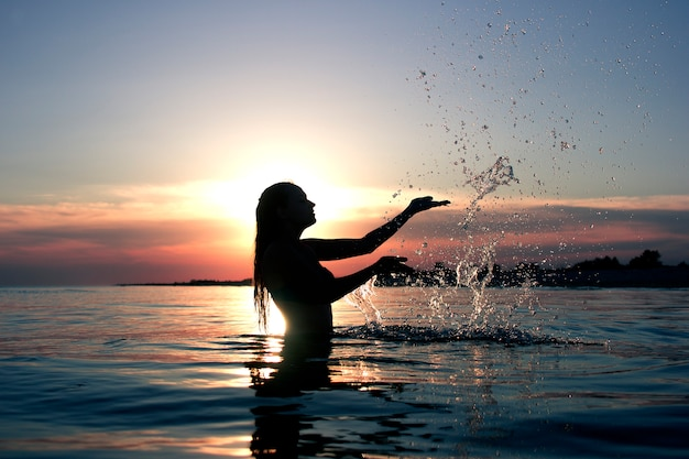 La siluetta femminile al tramonto sul mare fa una spruzzata dell'acqua