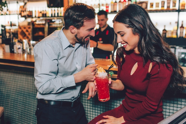 La simpatica e giovane coppia sta in piedi oltre allo stand del barista. sembrano timidi ma felici. inoltre stanno sorridendo e ridendo.