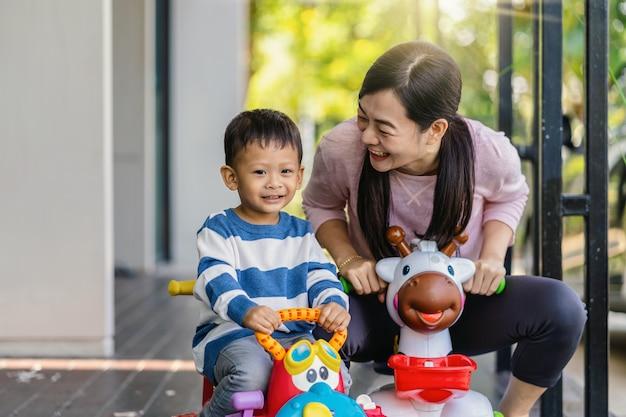 La singola mamma asiatica con il figlio sta giocando insieme al giocattolo dell'automobile quando vivono nella casa moderna