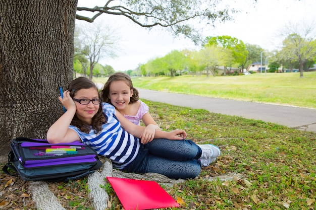 La sorella licenzia le ragazze rilassate sotto il parco degli alberi dopo la scuola