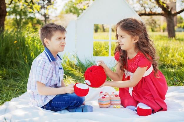 La sorellina del fratello versa il tè in un pic-nic. il concetto di infanzia e stile di vita.